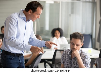 Angry boss scolding frustrated incompetent employee at workplace, dissatisfied leader shouting, pointing finger at bad office worker for bad work, laziness, sad man getting reprimand, job loss concept