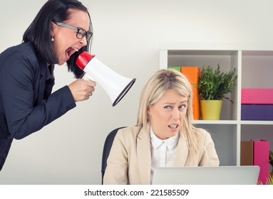Angry boss shouting at employee on megaphone