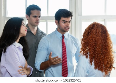 Angry boss talking to lazy employee at office of start up company