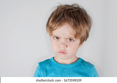 Angry boy frowning, looking forward. Light background. Closeup