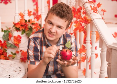 angry boy sits on the porch of his house decorated for Halloween. he is holding a toy Apple pierced with sharp iron screws. a young man tries to use voodoo magic.