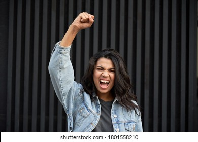 Angry brave African young woman standing on black background raising fist and screaming. Mixed race lady activist feminist leader fight for women rights, gender equality, empowerment protest concept.