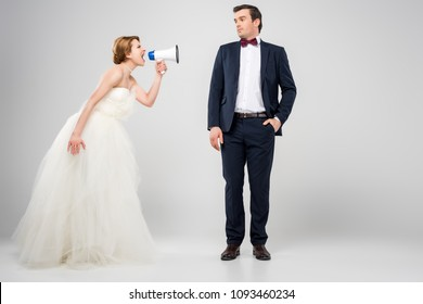 angry bride with megaphone yelling at groom, isolated on grey, feminism concept