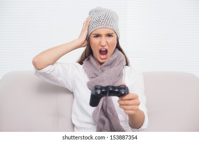 Angry brunette with winter hat on playing video games sitting on cosy sofa