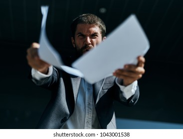 angry business man with documents on building background, street