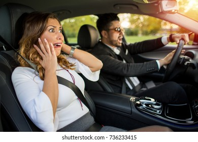 Angry business man with sunglasses driving and honking  while woman is afraid