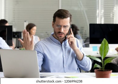 Angry business man talking on phone disputing looking at laptop, stressed frustrated office worker arguing by mobile solving online computer problem with technical support complaining on bad service