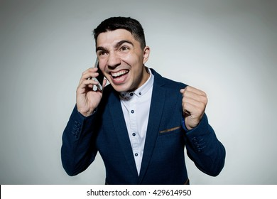 Angry business man talking on the phone isolated on a grey background.Human emotion, facial expression, feeling attitude.