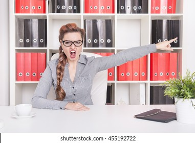Angry business woman boss pointing out in office. Dismissal concept