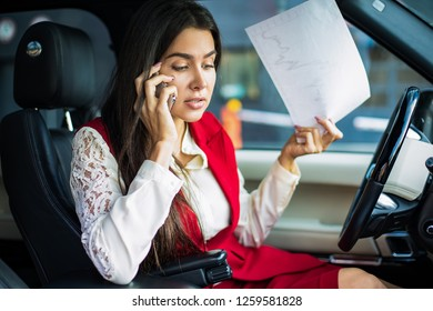 Angry business woman dressed in formal wear having bad serious cell telephone conversation with employee and holding in hand paper documents with financial charts while sitting in automobile car