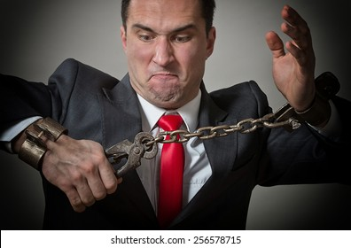 Angry businessman breaking the shackles on his hands