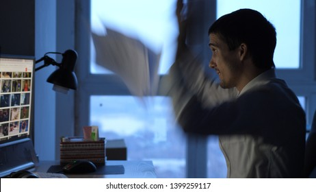 Angry businessman in formalwear working on computer in office at night, throws papers.