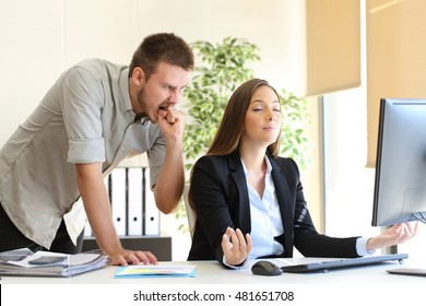 Angry businessman hating to his relaxed colleague at office