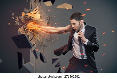 An angry businessman hitting concrete wall