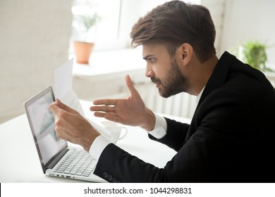 Angry businessman indignant disagree with information in mail business letter, annoyed disgruntled entrepreneur frustrated stressed by high taxes bill or past due unpaid debt, bad financial results