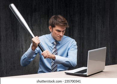 Angry businessman with laptop and bat
