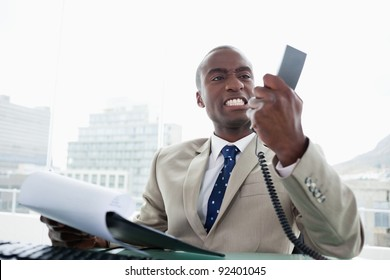 Angry businessman looking at his phone handset in his office