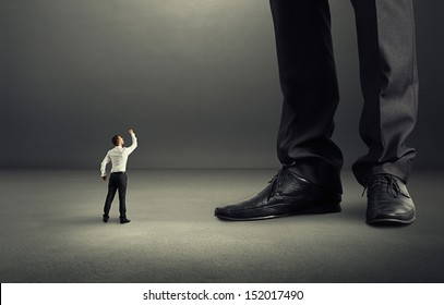 angry businessman looking up and showing fist to his big boss
