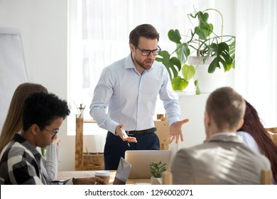 Angry businessman manager boss shouting at group office meeting scolding employees mad about business failure, corporate problem, bad work result, dissatisfied male executive criticizing staff workers