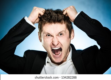 Angry businessman pulls his hair out and shouting