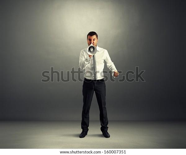 angry businessman screaming at megaphone