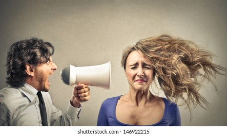 angry businessman screaming with megaphone to a woman