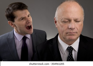 Angry Businessman Shouting At Calm Businessman