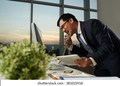 Angry businessman shouting in telephone receiver