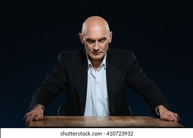 Angry businessman sitting at the table and looking at camera over black background
