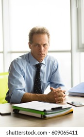 Angry businessman sitting at table and looking at camera in office. Boss of company going to have interview with new workers. Handsome man sitting with clasped hands.