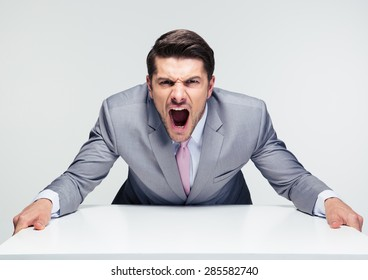 Angry businessman sitting at the table and screaming over gray background. Looking at camera