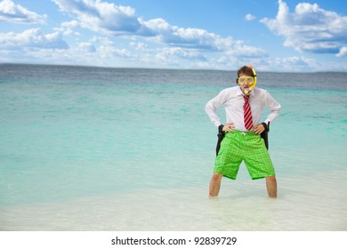 Angry businessman standing in the water on the beach with flippers