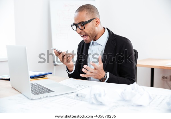 Angry businessman in stress working and talking on mobile phone at office desk
