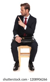 angry businessman threatening with his index finger looks to side while sitting on wooden chair on white background, full length picture