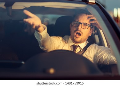 Angry businessman yelling out car window at sunset