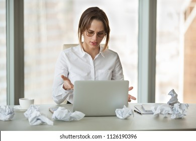 Angry businesswoman annoyed by stuck laptop working on urgent report till deadline at office desk with crumpled paper, mad stressed employee feels frustrated about data loss or computer crash