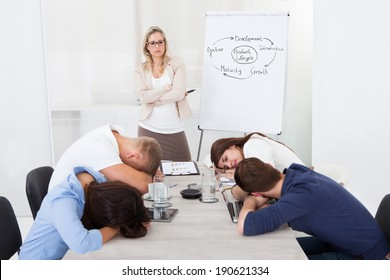 Angry businesswoman looking at tired colleagues sleeping during presentation in office