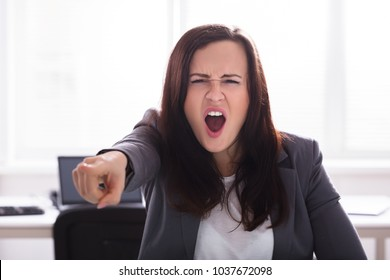 Angry Businesswoman Shouting And Pointing Finger In Office