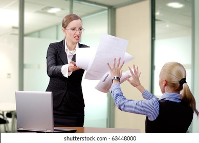 Angry businesswoman throwing papers in her partner