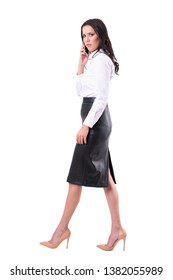 Angry busy business woman walking, talking on phone and looking at camera. Side view. Full body isolated on white background.