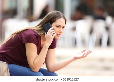 Angry casual woman calling on the phone sitting on a bench in the street