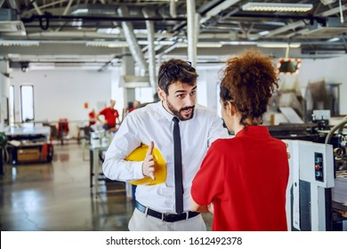 Angry caucasian bearded director in shirt and tie arguing with his sloppy female employee. Printing shop interior.