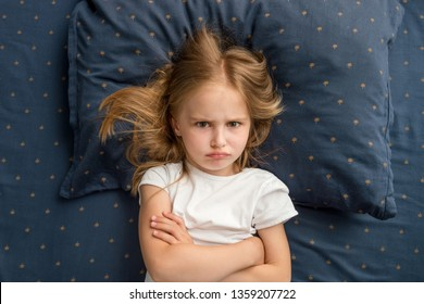 Angry child girl lying on the bed with crossed hands and refuses to sleep