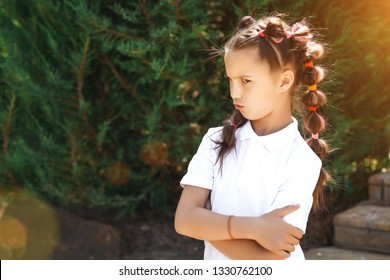 angry child girl with pigtails wearing white shirt in a sunny summer park. pine trees on a background
