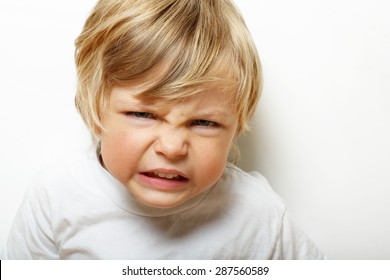 Angry child on white background.