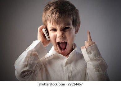 Angry child screaming on the mobile phone