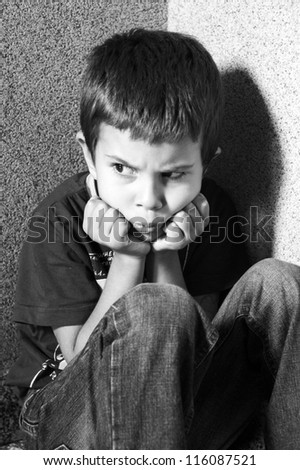 an angry child sitting in a corner in black and white