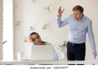 Angry confused boss catching sleeping employee at workplace, lazy sleepy woman napping instead of work, misconduct wasting time in office, mentor waking up exhausted overworked intern dozing