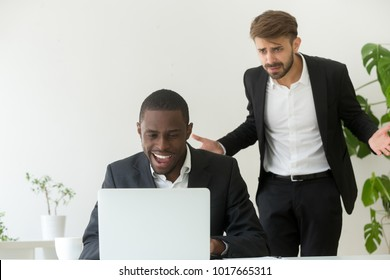 Angry confused white boss catching african american employee entertaining online instead of work, indignant caucasian executive perplexed by lazy office worker misconduct wasting time at workplace