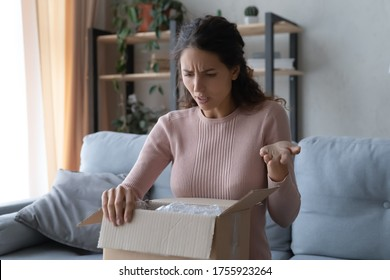 Angry confused woman unpacking parcel, wrong or broken online store order, sitting on couch at home, dissatisfied female looking in cardboard box, bad delivery service, displeased by post shipping